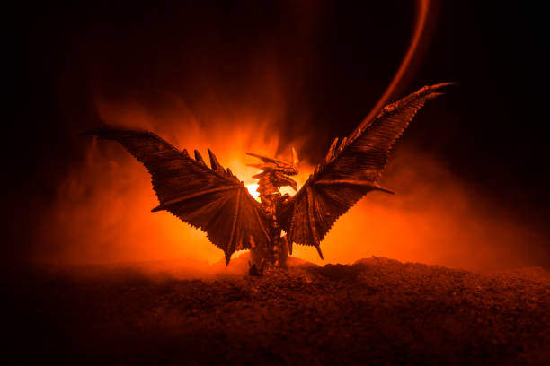 Silhouette of fire breathing dragon with big wings on a dark orange background Silhouette of fire breathing dragon with big wings on a dark burning fire background. Selective focus dragon stock pictures, royalty-free photos & images