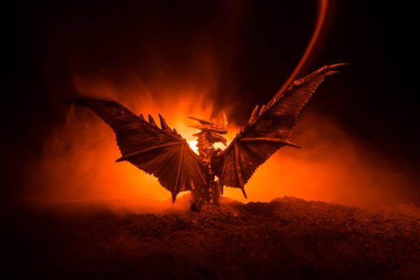 silueta de dragón que respiraba fuego con grandes alas sobre un fondo naranja oscuro - dragón fotografías e imágenes de stock