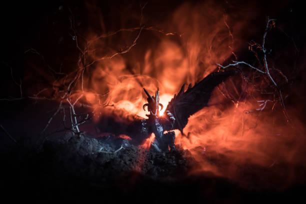 Silueta de dragón que respiraba fuego con grandes alas sobre un fondo naranja oscuro. Imagen de horror - foto de stock