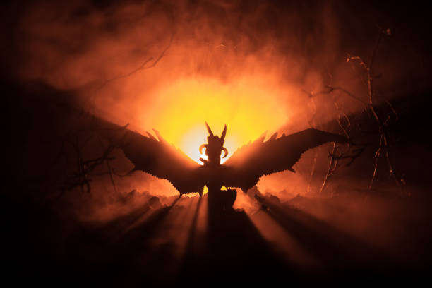 Silhouette of fire breathing dragon with big wings on a dark orange background. Horror image stock photo