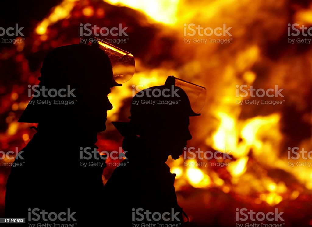 Silhouette of firefighters against large fire in the dark stock photo