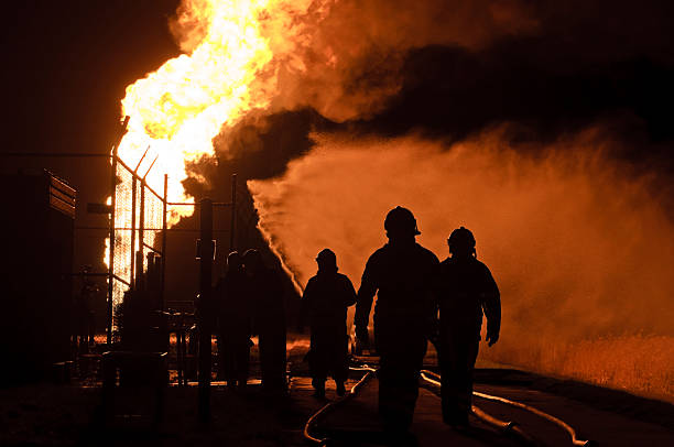 silhouette di vigili del fuoco in azione di notte - foto stock