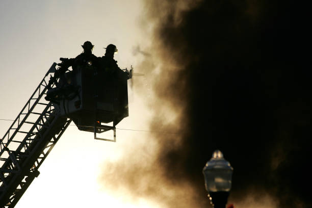 Silhouette of Firemen in a basket lift stock photo