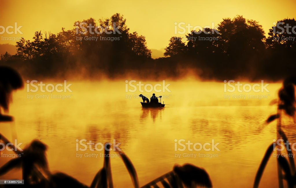 Silhouette of fisher and dog sitting in boat stock photo