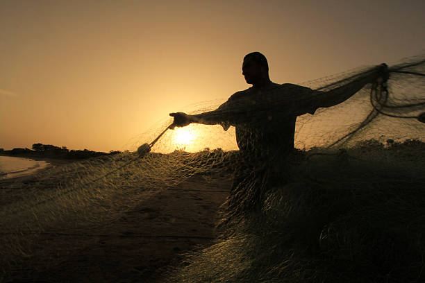 Silhouette of fisherman pulling fishing nets at Derrumbao Beach stock photo