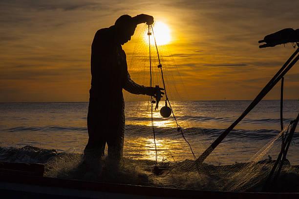 シルエットの漁師の日の出を背景に - 漁師 ストックフォトと画像