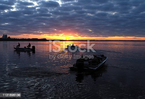 Unrecognizable Silhouette of Fisherman Heading Out to Their Favorite Fishing Sites at Sunrise on a Florida Lake