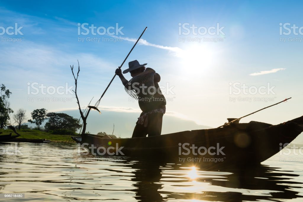 Silhouette of fishermen using coop-like trap catching fish in lake with beautiful scenery of nature morning sunrise. Beautiful scenery at Bang-Pra, Chonburi Province Thailand. stock photo