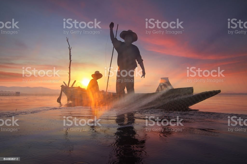Silhouette of fishermen using nets to catch fish at the Bangpra lake with beautiful scenery of nature during sunrise time. Bang Pra Reservoir at Chonburi province in Thailand stock photo