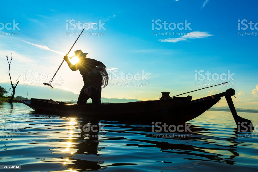 Silhouette of fishermen using nets to catch fish at the lake in the morning stock photo