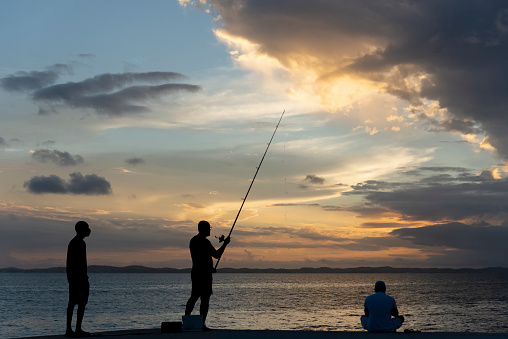 Salvador, Bahia, Brazil - April 18, 2021: Silhouette of fishermen with their fishing poles on the rocks in search of fish.
