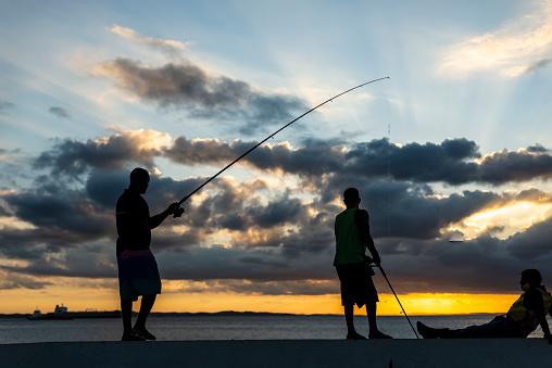Salvador, Bahia, Brazil - May 23, 2021: Silhueta de pescadores com suas varas de pesca sobre as rochas em busca de peixes.