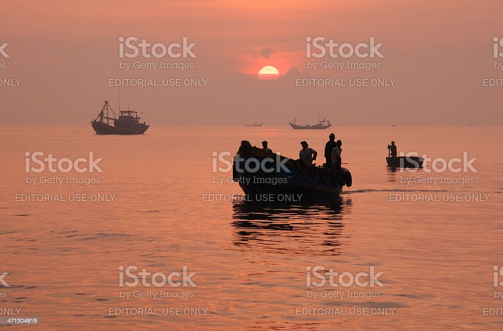 Silhouette of fishing boat return to port after a night royalty-free stock photo