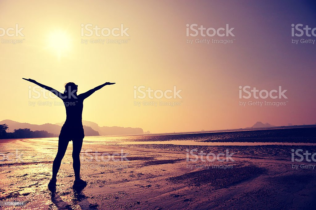 Silhouette of fit woman with arms spread out at beach stock photo