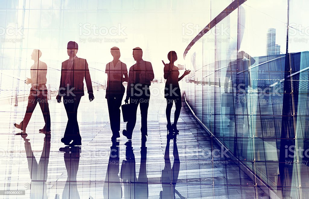 Reflection of five adults in business attire walking and interacting....