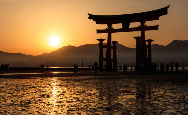 Silhouette of floating Torii Gate at sunset, Miyajima island, Hiroshima, Japan Miyajima, Japan - April 9, 2016 : The great Torii, was built in 1875. shinto shrine stock pictures, royalty-free photos & images