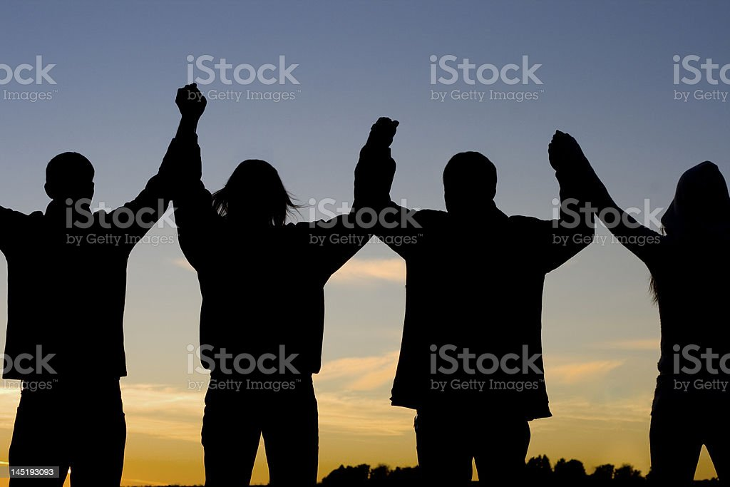 Silhouette of four people holding hands up in triumph stock photo