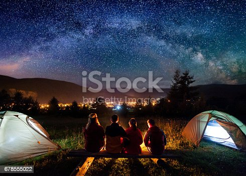 678554980 istock photo Silhouette of four people sitting on a bench made of logs and watching fire together beside camp and tents in the night. On the background starry sky, Milky way, mountains and luminous town. Rear view 678555022