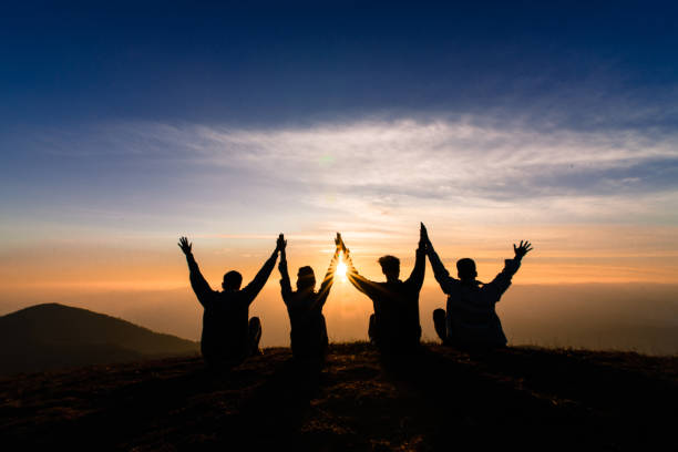 silhouette of friends shake hands up and sitting together in sunset for happiness,business successful and team work concept. silhouette of friends shake hands up and sitting together in sunset for happiness,business successful and team work concept. central america stock pictures, royalty-free photos & images