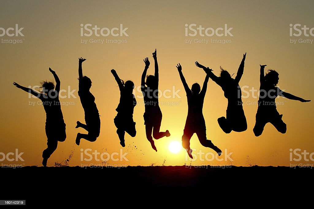 Silhouette of friends simultaneously jumping royalty-free stock photo