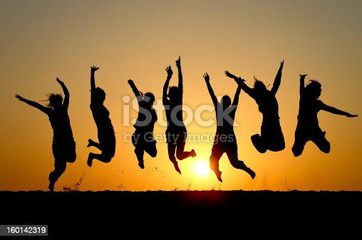 istock Silhouette of friends simultaneously jumping 160142319