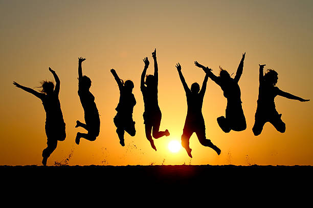 Silhouette of friends simultaneously jumping stock photo