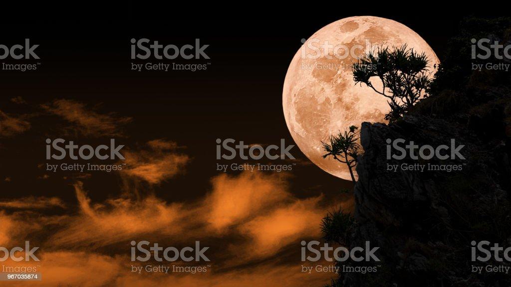 Silhouette des vollen blaues Blutmond hinter Felswand mit orangefarbenen himmel hintergrund – Foto