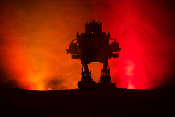 Silhouette of Giant robot. Futuristic tank in action with foggy fire sky background Silhouette of Giant robot. Futuristic tank in action with foggy fire sky background. Combat vehicle. electricity transformer stock pictures, royalty-free photos & images