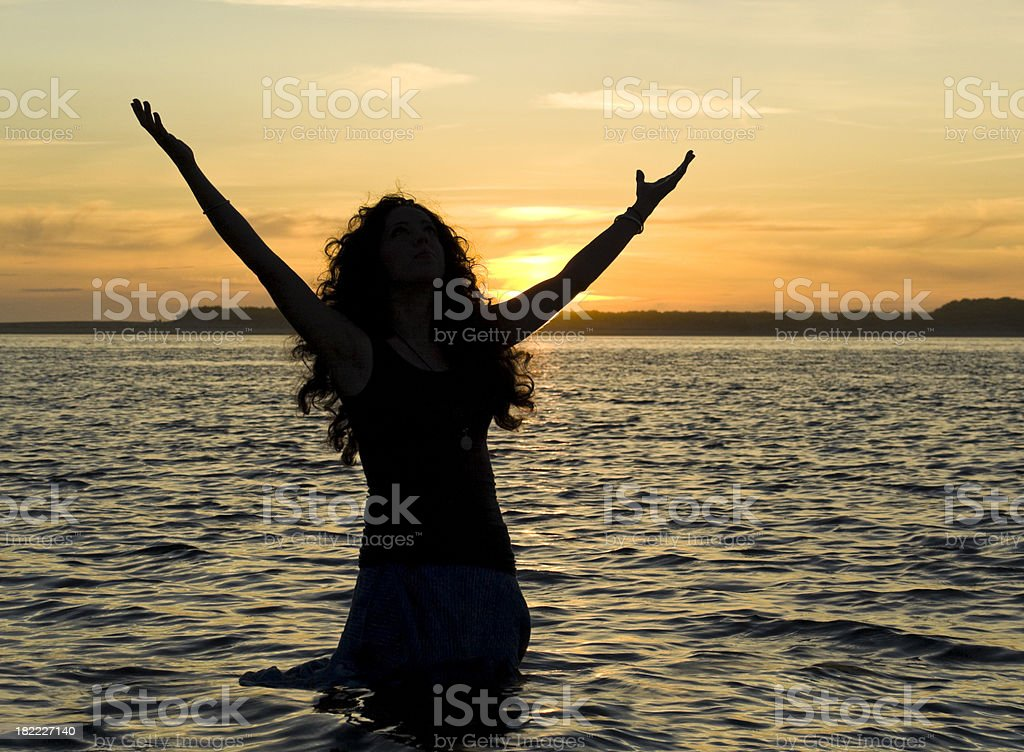 Silhouette of girl at sunset with arms in air by the sea royalty-free stock photo