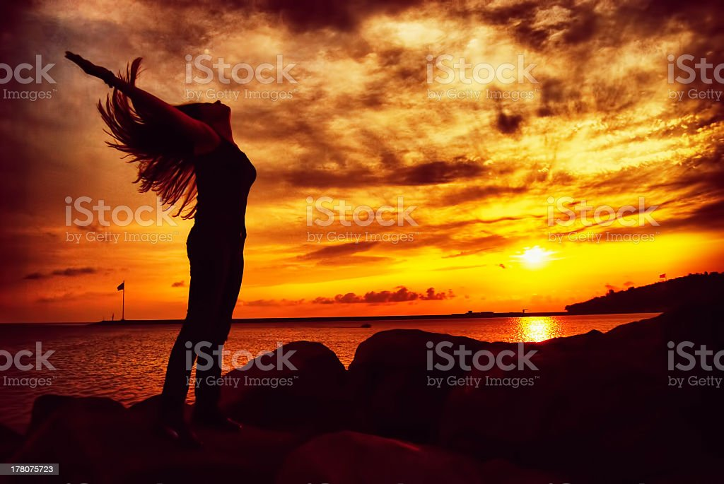 Silhouette of Girl Expressing Joy at Sunrise or Sunset royalty-free stock photo