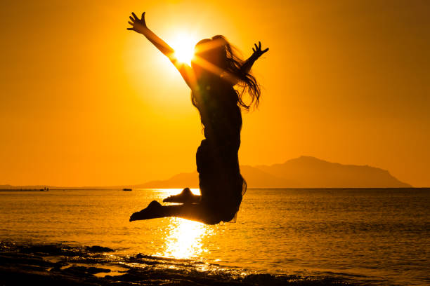 silhouette of girl jumping against sunrise - african youth jumping for joy stock photos and pictures