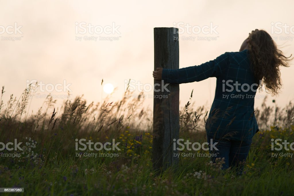 Silhouette of Girl leaning from post stock photo