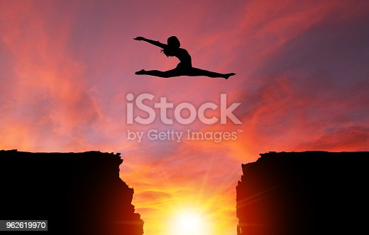 Silhouette of girl dancer in a split leap over dangerous cliffs with dramatic sunset or sunrise background and copy space. Concept of faith, conquering adversity, taking risk; challenge, courage, determination or achievement.  Please note the sunset background was shot in Calgary on 10-24-2017 (reference image attached).  The dancer model was shot in studio on 04-07-2016 (Reference image attached and Model Release also attached). The dance model was isolated in Photoshop and then composited onto the sunset background as a silhouette.