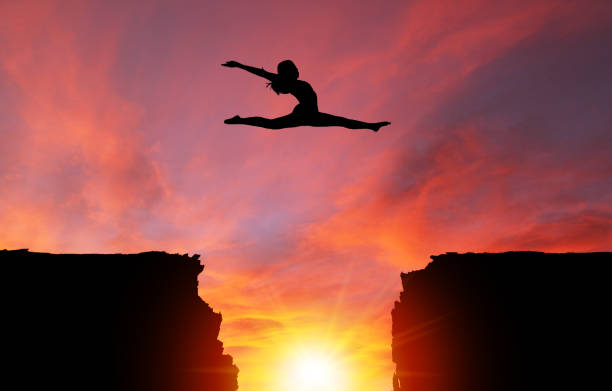 Silhouette of Girl Leaping Over Cliffs With Sunset Landscape Silhouette of girl dancer in a split leap over dangerous cliffs with dramatic sunset or sunrise background and copy space. Concept of faith, conquering adversity, taking risk; challenge, courage, determination or achievement.  Please note the sunset background was shot in Calgary on 10-24-2017 (reference image attached).  The dancer model was shot in studio on 04-07-2016 (Reference image attached and Model Release also attached). The dance model was isolated in Photoshop and then composited onto the sunset background as a silhouette. ravine stock pictures, royalty-free photos & images