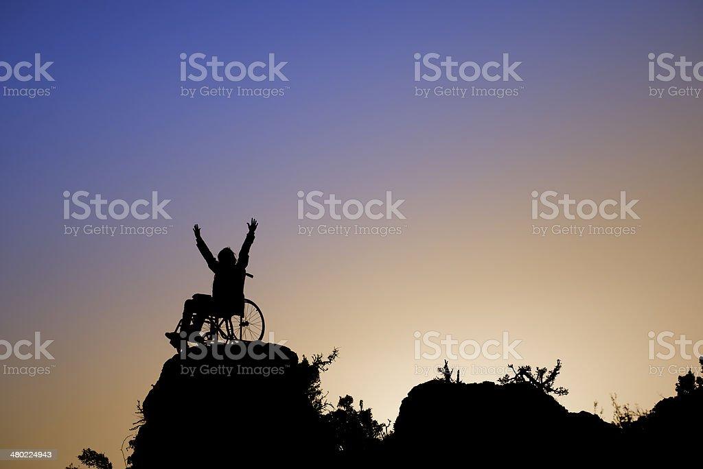 Silhueta de menina em uma cadeira de rodas - foto de acervo