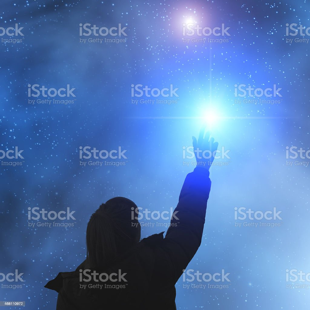 Silhouette of girl reaching for the stars stock photo