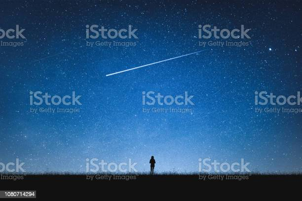 Photo of Silhouette of girl standing on mountain and night sky with shooting star. Alone concept.