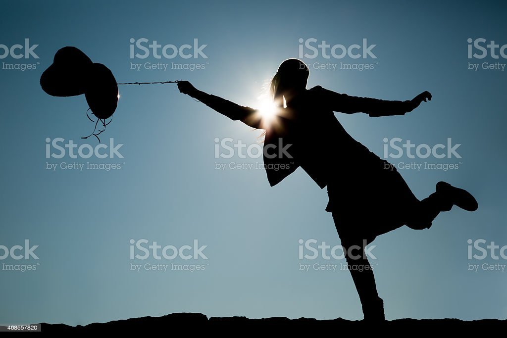 Silhouette of girl with balloons on a string stock photo