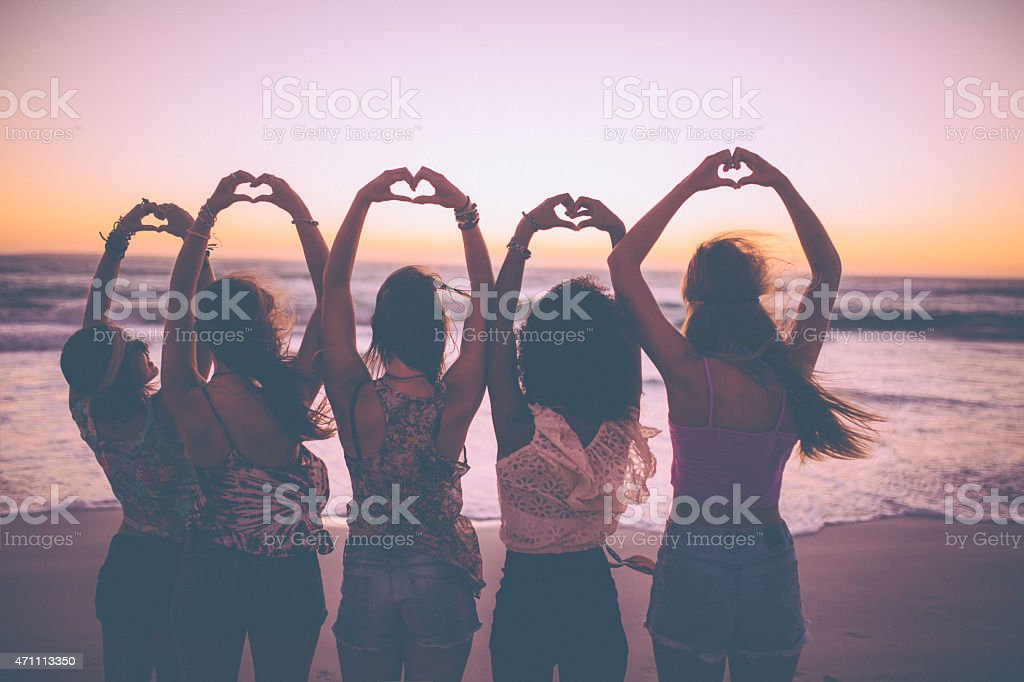 Silhouette of girls making heart shapes with their hands stock photo