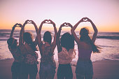Silhouette of girls making heart shapes with their hands
