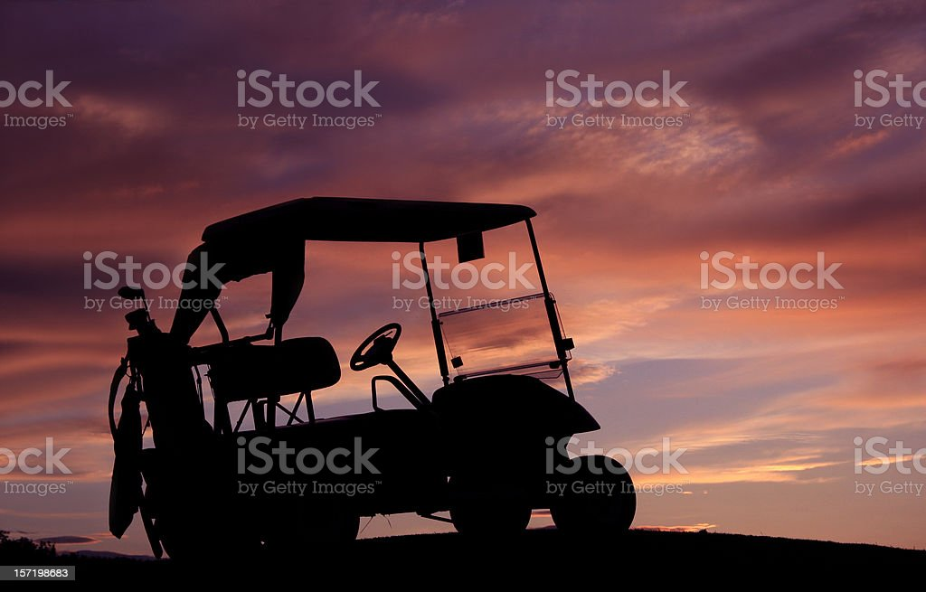 Silhouette of golf cart in front of orange and purple sunset royalty-free stock photo