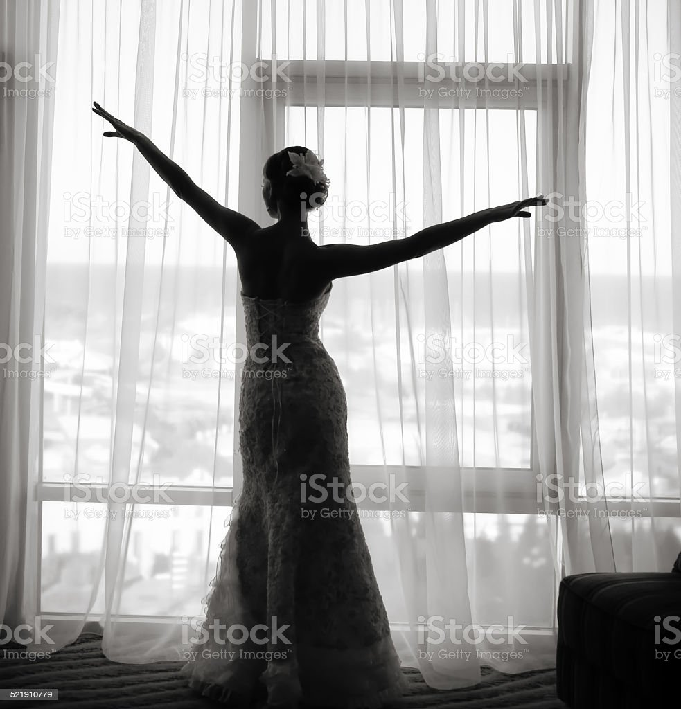 Silhouette of gorgeous bride in hotel room. stock photo