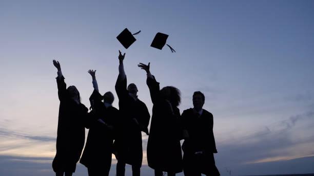 silueta de estudiantes graduados lanzando gorras al aire - graduation fotografías e imágenes de stock