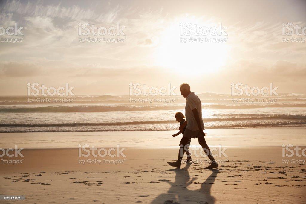 Silueta del abuelo caminando por la playa con su nieto - foto de stock