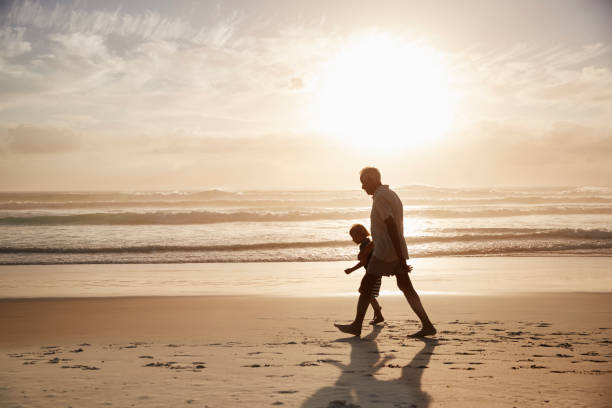 Silhouette Of Grandfather Walking Along Beach With Grandson Silhouette Of Grandfather Walking Along Beach With Grandson grandson stock pictures, royalty-free photos & images