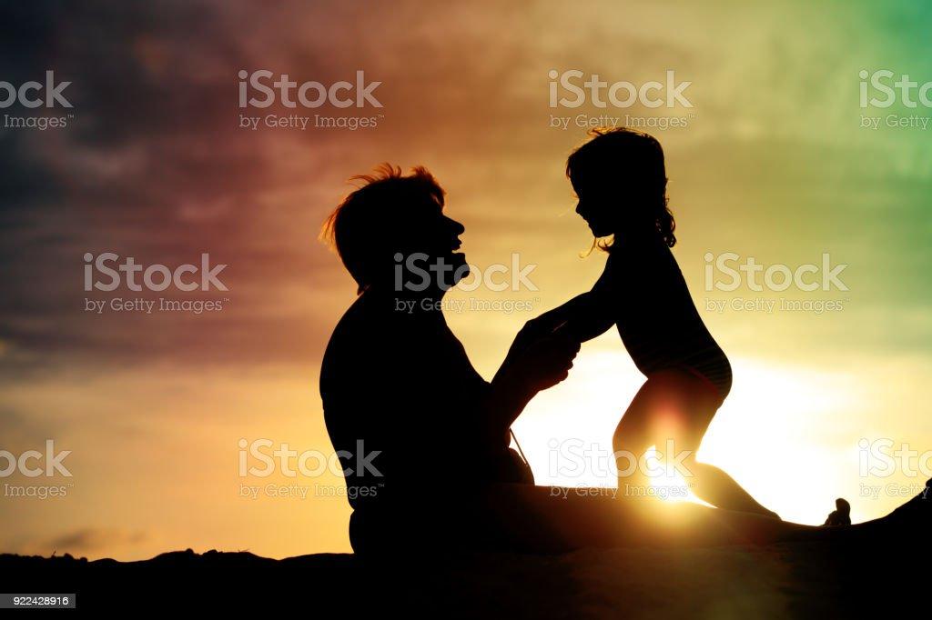 silueta de abuela y nieta juega en la playa al atardecer - foto de stock