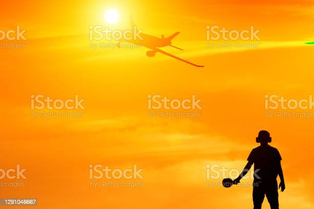 Photo of Silhouette of ground staff sending airplane taking off flight with orange sky background and lens flare effect