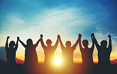 Silhouette of group business team making high hands over head in sunset sky evening time for business success and teamwork concept in company growth mergers and acquisitions start greeting etiquette