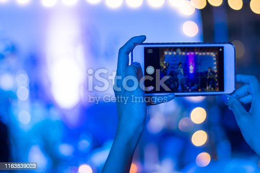 Silhouette of guest hands using smartphone as camera to take pictures and videos of wedding ceremony on stage with bokeh light. Audience taking photo of concert or events by mobile phone at night.