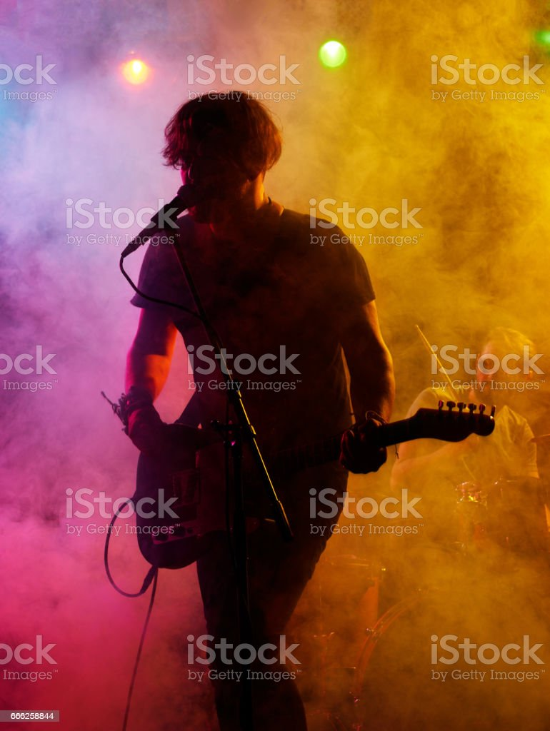 Silhouette of guitar player on stage. stock photo